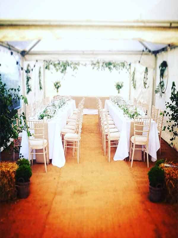 Two rows of tables in a party tent for a small garden